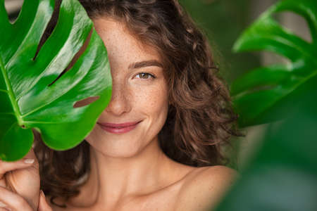 Close up face of beautiful young woman covering her face by green monstera leaf while looking at camera. Natural smiling girl with green palm leaf. Portrait of beauty woman with natural makeup and freckles on skin standing behind big green leaves. Banque d'images