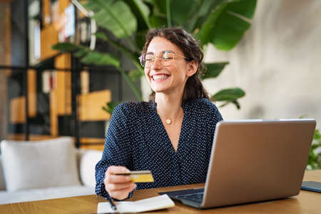 Young happy woman doing shopping online with her laptop at home. Portrait of excited woman holding credit card and buy on an e-commerce site with copy space. Beautiful laughing girl paying online bills using debit card and computer. Banque d'images