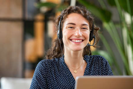 Portrait of smiling casual businesswoman working in a creative office. Smiling friendly woman working as call center agent for online support. Young woman in video call with headphones looking at camera.