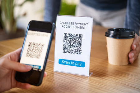 Customer scanning tag in coffee shop to pay online. Close up of woman hand holding smartphone and scanning qr code for cashless payment at cafeteria. Girl framing qr code in coffee shop to make a purchase, small business accepts digital payment.