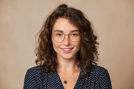 Beautiful young woman wearing eyeglasses isolated on background and looking at camera. Proud female student with nerd glasses isolated on wall. Sophisticated glamor girl in shirt wearing big spectacles and smiling.