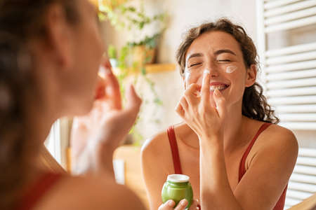 Playful young woman applying cream on nose. Cheerful girl holding green lotion jar standing in front of mirror applying moisturizer on nose. Beautiful woman taking care of skin by applying moisturizer every day in the morning. Banque d'images