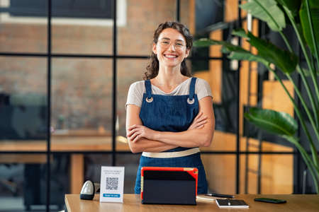 Portrait of cheerful cafe owner in uniform standing with arms crossed and digital tablet, qr code and nfc machine on table. Successful woman in modern cafeteria wearing blue apron and looking at camera. Satisfied and proud girl with spectacles standing near table.