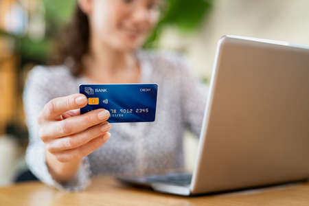 Close up hand of young woman holding credit card while making online payment. Woman hands holding a debit card and using laptop to do online shopping. Smiling girl with bank card paying bills online.
