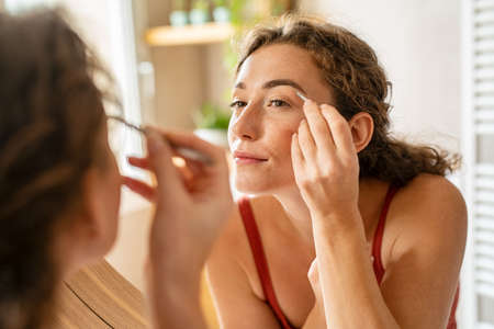 Beautiful young woman using tweezer on eyebrows. Pretty girl raising eyebrows using plucker before makeup. Beauty woman shaping eyebrows while looking in mirror. Banque d'images