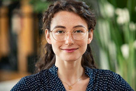 Portrait of young woman wearing spectacles and looking at camera. Close up face of happy girl with glasses smiling at work. Confident and satisfied businesswoman wearing eyeglasses in office. Banque d'images