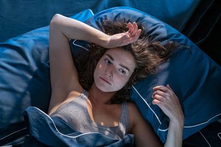 Young stressed woman lying on bed late at night suffering from insomnia, sleep apnea or stress. Top view of depressed girl lying bed with dark pillow and blue blanket late at night. High angle view of awake girl in the middle of the night. Banque d'images