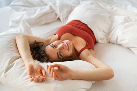 Top view of happy young woman waking up after sleep. Portrait of beautiful smiling woman lying in bed under white blanket at morning. High angle view of smiling natural girl feeling fresh after a good rest and looking at camera.