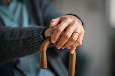 Close up of senior disabled woman hands holding walking stick. Detail of old woman hands holding handle of cane. Old lady holding walking stick.