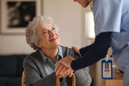 Old woman talking with a female doctor while holding hands at home. Smiling senior woman talking to her general practitioner visiting her at home during virus epidemic. Happy old patient holding hands of caregiver at nursing home.