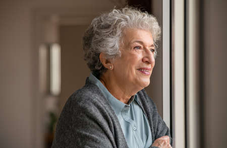 Smiling old woman with grey hair looking through the window. Happy senior woman standing near window during quarantine due . Retired and contemplative lady wearing sweater while looking outside and thinking.