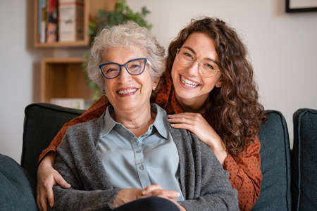 Portrait of old grandma and adult granddaughter hugging with love on sofa while looking at camera. Happy young woman with eyeglasses hugging from behind older grandma with spectacles. Senior woman spending time with her beautiful daughter, generation family concept.