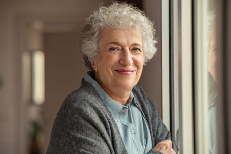 Portrait of happy senior woman standing at home near window and looking at camera. Smiling beautiful old woman relaxing at home during Covid quarantine standing near window. Cheerful retired old lady relaxing at home. Banque d'images