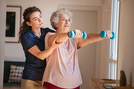 Old woman training with physiotherapist using dumbbells at home. Therapist assisting senior woman with exercises in nursing home. Elderly patient using dumbbells with outstreched arms in a physical therapy session in clinic.