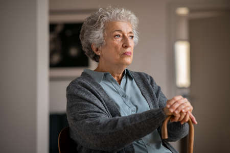 Retired unhappy woman with her wooden walking stick at home. Lonely serious senior woman holding walking cane and looking through the window. Moody and upset grandmother sitting on couch in nursing home. Banque d'images