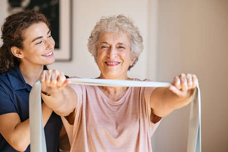 Young female trainer assisting senior woman with resistance band. Rehabilitation physiotherapy worker helping old patient at nursing home. Old smiling woman with stretch band being coached by personal trainer or physiotherapist in clinic.