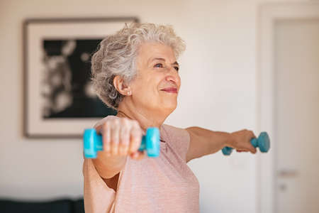 Senior woman lifting weights and working out at home. Old woman doing arms stretching exercise using weight dumbbells. Retired lady exercising with light weights. Banque d'images