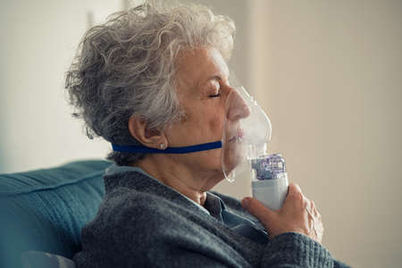 Portrait of a ill senior woman making inhalation at home. Close up of an elderly woman holding mask nebulizer inhaling fumes medication into lungs with closed eyes. Self treatment of the respiratory tract using inhalation nebulizer. Banque d'images
