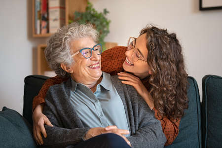 Old grandmother and adult granddaughter hugging at home and looking at each other. Happy senior mother and young daughter embracing with love on sofa. Happy young woman hugging from behind grandma with love.