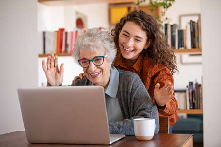 Cheerful granddaughter with grandmother sitting at home and waving hand during video call using laptop. Senior woman with cheerful daughter using laptop during lockdown. Old woman sitting with her adult granddaughter looking at laptop making a videocall while waving hands.