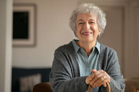 Portrait of smiling mature woman holding walking stick and sitting on chair at home. Portrait of happy senior woman under quarantine during  pandemic smiling while looking at camera. Old retired lady with grey and white hair stay at nursing home with copy space.
