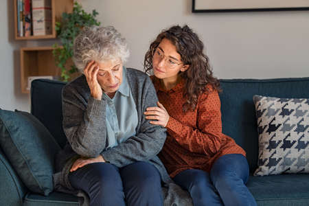Caring daughter comforting frustrated unhappy senior woman. Loving adult granddaughter talking to sad depressed old grandmother holding hand and comforting her. Upset widowed woman with headache consoled by her daughter. Banque d'images