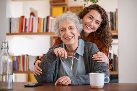 Cheerful young woman embracing senior mother at home and looking at camera. Portrait of happy adult granddaughter and grandmother embracing and smiling together. Portrait of lovely young woman hugging from behind elderly granndma.