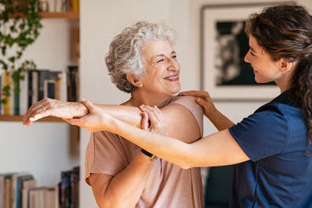 Happy senior woman doing exercise at home with physiotherapist. Young gym trainer helping elderly smiling woman exercising at home. Old retired lady doing stretching arms at home with the help of a personal trainer during a rehabilitation session. Banque d'images