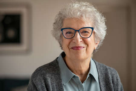 Portrait of happy retired senior woman looking at camera while wearing new eyeglasses. Smiling satisfied old woman wearing spectacles at home. Closeup face of wrinkled beautiful grandmother trying on new eyewear while looking at camera. Banque d'images