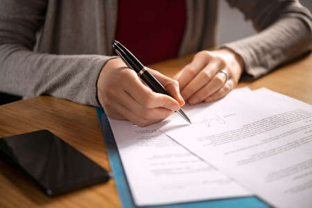 Close up of hands of young woman signing legal documents on desk. Close up of woman hand holding pen and signing legal paper seated at desk. Detail of lawyer filling official document, deal done.