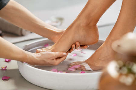 Young woman having her feet scrubbed in beauty salon. Close up of hands of young masseur washing feet of woman in spa in grey bowl with water and pink petals. Girl getting spa massage treatment in luxury beauty salon: foot reflexology and chiropody therapy.