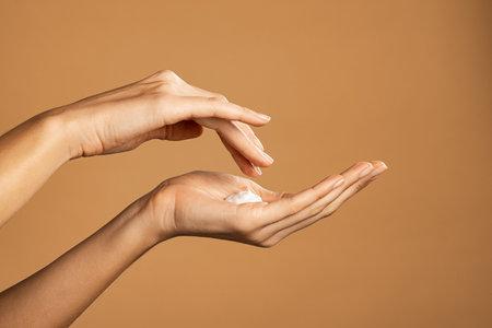 Close up shot of beautiful female hands holding and applying moisturiser. Beauty woman hand applying cream. Beautiful girl on creamy background holding moisturizer.