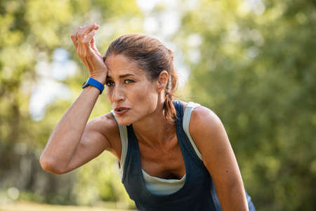 Exhausted mature woman after jogging catching her breath. Sweaty middle aged athlete taking a break from running at park with copy space. Tired mid adult woman wipes wet forehead after intense fitness training. Stock fotó