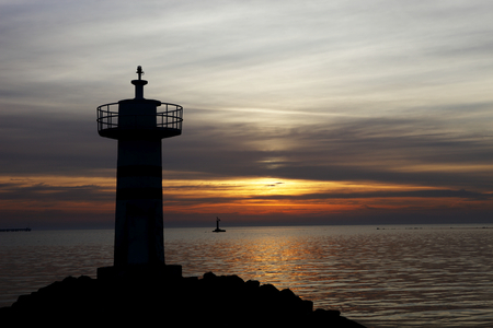 the color image: sunrise photographed lighthouse in silhouette, color image Stock Photo