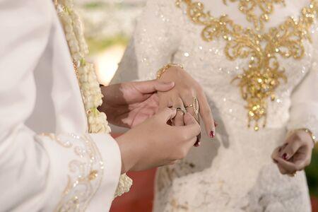 Pasang Cincin on Javanese Wedding. Traditional Javanese Groom Puts a Ring On The Bride 版權商用圖片