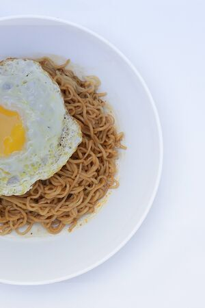 Fried noodle (Indomie Goreng) with sunny side up egg, served on white plate. Top view close up detail Stock Photo