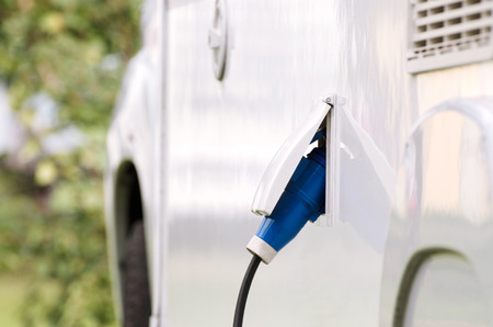 White electric car is charging by ecological power. photo