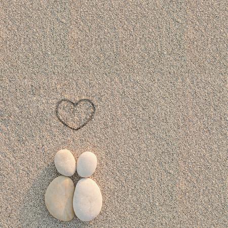 amantes: Guijarros shapes amantes con el coraz�n en la arena Foto de archivo