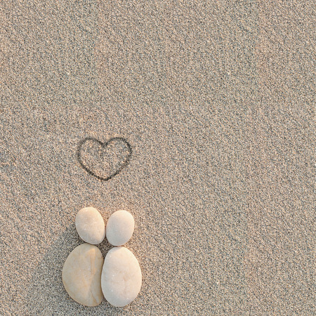 Pebbles shapes lovers with heart on the sand Stock Photo