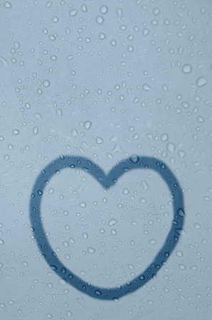 tarnished: Shape of heart is drawed on a fogged window glass with drops.