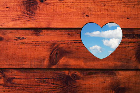 Pattern for text or card consists heart shaped hole with blue sky and white clouds in a brown wooden wall. photo