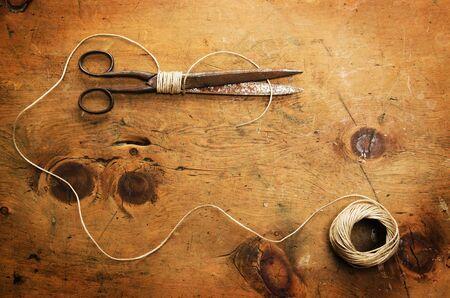 work tools: mesa de madera vieja con hilo y tijeras hace un marco para el texto en estilo r�stico de la vendimia. Vista superior. el concepto de fondo retro. Foto de archivo