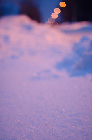 snow road: Snow road at night with a glowing defocused electric lights on the background. Selective focus. Stock Photo