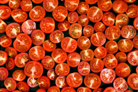 recipe background: Fresh red tomatoes halves on black pan. Design element for web background, recipe, catalog print, web use. Top view.