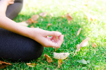 Woman meditating and sitting in a cross-legged position on the grass. Padmasana, lotus pose, hatha yoga. Stok Fotoğraf - 154096023