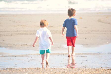 younger: Younger Brother Follows Boy Along Ocean Shore Stock Photo
