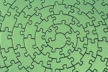 complete green jigsaw - pieces fitting together in form of a spiral
