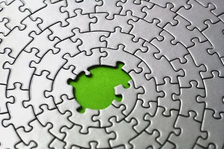 silver jigsaw with missing pieces in the center - shallow DOF, focus is on and over the missing pieces Stock Photo