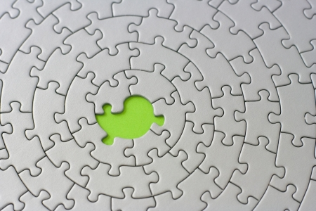 fitting in: grey jigsaw with one missing piece - pieces fitting together in form of a spiral