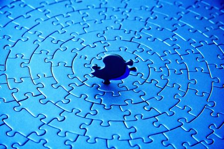 abstract of a blue jigsaw with the last piece upstanding - pieces fitting together in form of a spiral photo